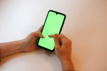 young girl pressing green screen of mobile phone with fingers on white table