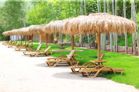 Sun umbrellas and relaxing pool at small hotel with chaise-longue Stock Photo