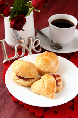Home made scones with strawberry jam and a cup of tea photo