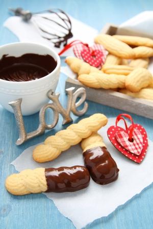 Galletas de mantequilla casera con chocolate y corazones en el fondo de madera azul