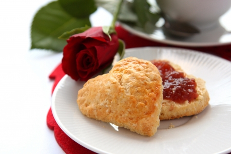 Heart shaped scones with strawberry jam and a cup of tea photo