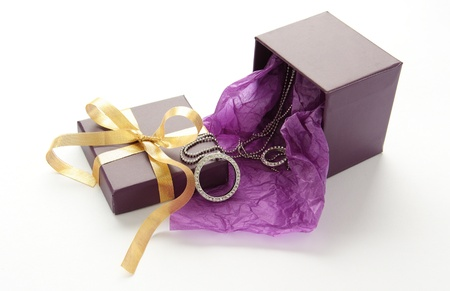 Purple gift box with jewelry and yellow ribbon over white Stock Photo - 17467833