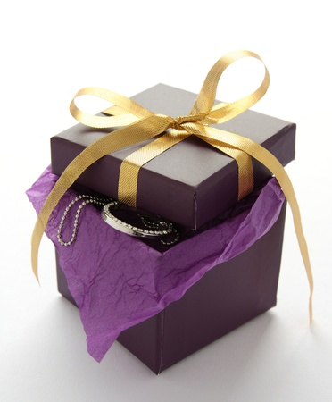 Purple gift box with jewelry and yellow ribbon over white photo