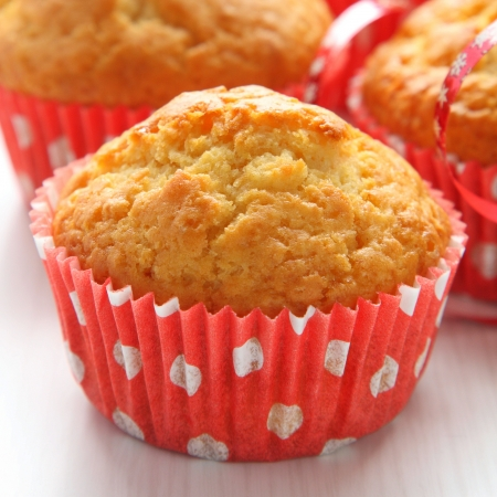 Muffins in red cups on white background