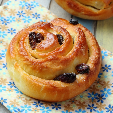 Fresh sweet swirl buns with raisins on colored wooden table Stock Photo