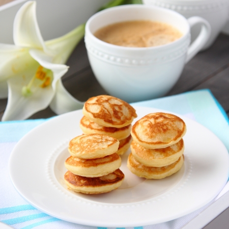 Freshly baked poffertjes - traditional Dutch little pancakes, selective focus Stock Photo