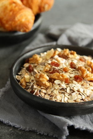Healthy homemade granola cereal with nuts and raisins on gray background Stock Photo