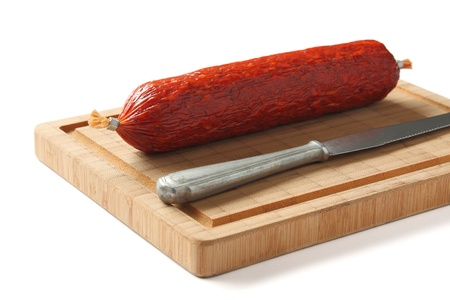Spanish chorizo sausage with knife on wooden board photo