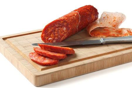 Spanish chorizo sausage with knife on wooden board, focus is on sausage photo