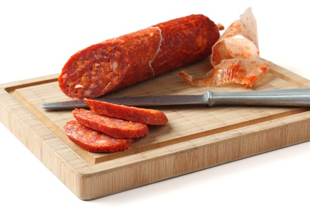 Spanish chorizo sausage with knife on wooden board, focus is on the sausage slices Stock Photo