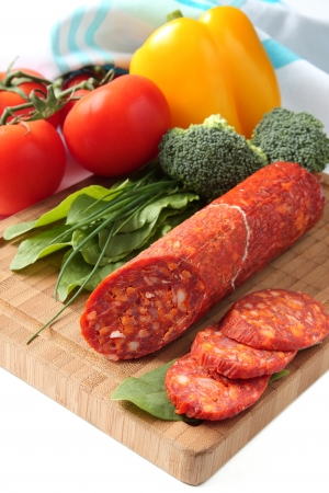 Spanish chorizo sausage with vegetables on a wooden board Stock Photo