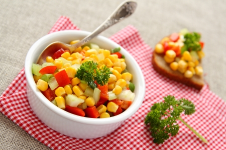 the corn salad: Homemade corn salsa in white bowl with spoon