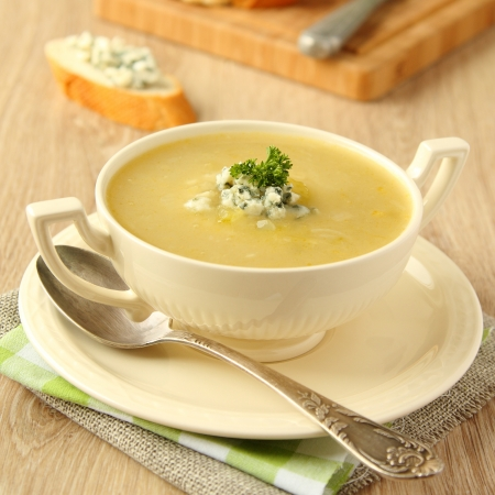 vegetable soup: Homemade onion soup with celery and blue cheese on wooden background Stock Photo