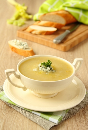 Homemade onion soup with celery and blue cheese on wooden background photo