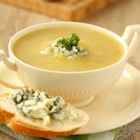 Homemade onion soup with celery and sliced bread with blue cheese on wooden background photo