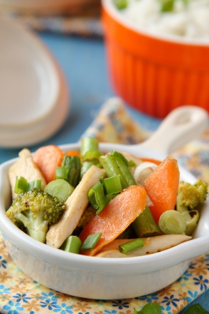 Chicken stir fry with vegetables (carrots, onions, broccoli, green beans) and rice Stock Photo