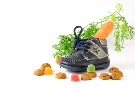 Childrens shoe with carrot for horse of Sinterklaas and pepernoten isolated over white
