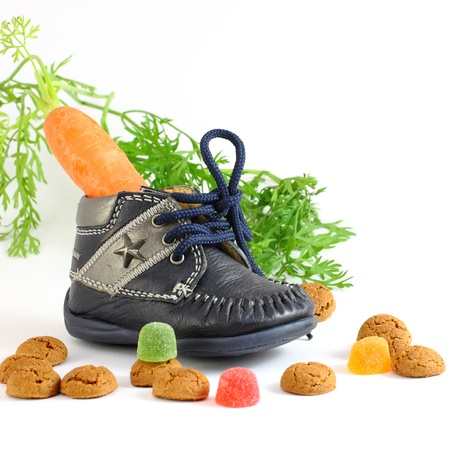 strooigoed: Childrens shoe with carrot for horse of Sinterklaas and pepernoten isolated over white