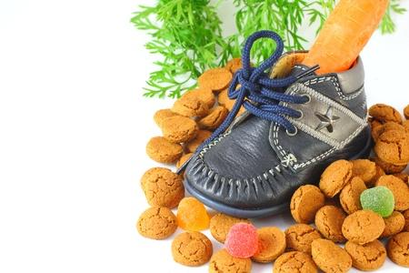 Childrens zapato con zanahoria para el caballo de Sinterklaas y pepernoten aislado m�s de blanco Foto de archivo