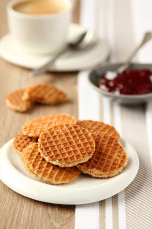 Mini stroopwafels (syrupwaffles) on a plate with cup of coffee and jam photo