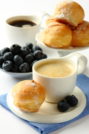 Cup of coffee with profiteroles and blueberries photo