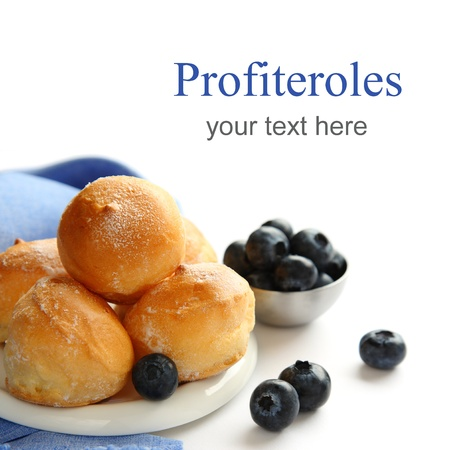 Profiteroles and blueberries over white with sample text photo