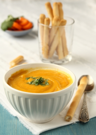 sweet course: Bowl of homemade carrot soup with coconut milk and coriander