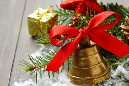 Golden bell with red satin ribbon bow and branch of christmas tree photo