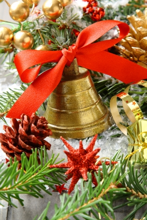 Golden bell with red satin ribbon bow and christmas decoration photo