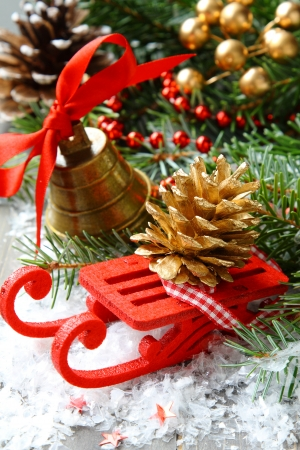 Christmas composition with sleigh, pinecone and bell photo