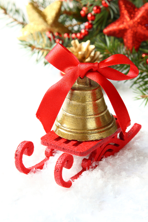 Christmas composition with sleigh and golden bell over white photo