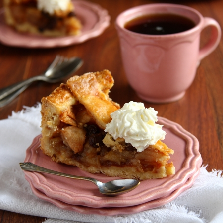 Slice of homemade dutch apple pie with whipped cream