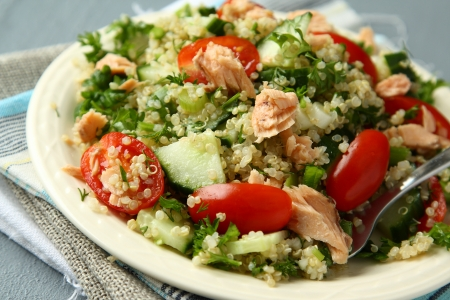Tabbouleh salad with quinoa, salmon, tomatoes, cucumbers and parsley photo
