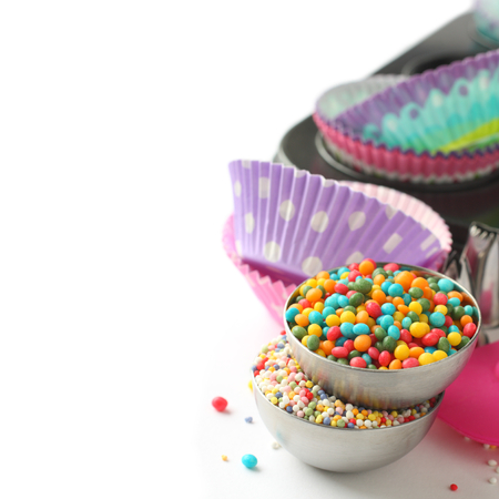 Candy sprinkles with cupcake cases and baking pan over white photo