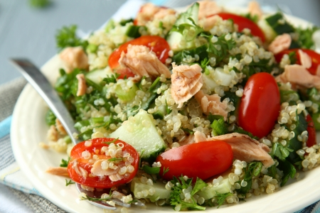Tabbouleh salad with quinoa, salmon, tomatoes, cucumbers and parsley Stock Photo