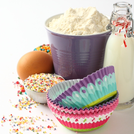 Cupcake cases and ingredients over white with copyspace photo