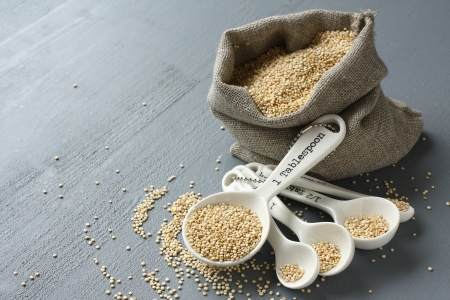 Quinoa grain in small burlap sack and porcelain measuring spoons photo