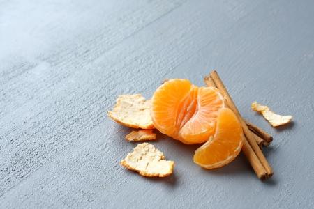 Abrir mandarina fresca con ramas de canela sobre fondo gris