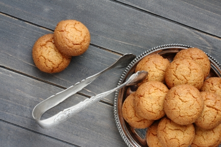 Almond cookies with sugar tongs on rustic wooden table