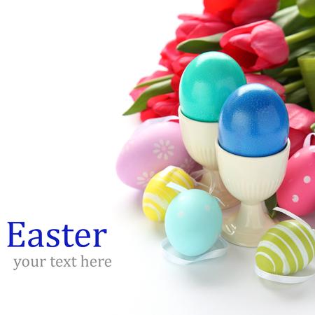 Huevos de pascua de colores y tulipanes de color rosa sobre blanco con texto de ejemplo