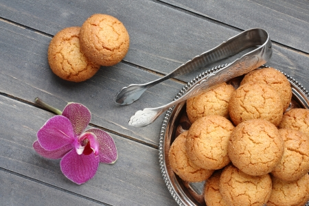 Almond cookies with sugar tongs and orchid flower on rustic wooden table photo
