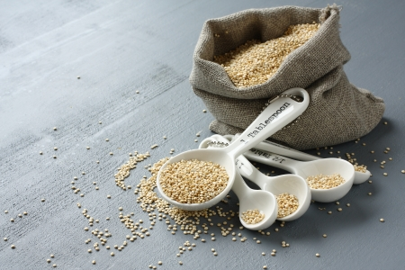 Quinoa grain in small burlap sack and porcelain measuring spoons on gray  photo