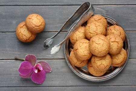 brown sugar: Almond cookies with sugar tongs and orchid flower on rustic wooden table