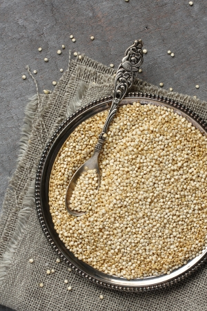 Uncooked quinoa in metal plate on wooden