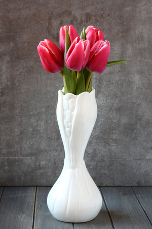 Ramo de tulipanes de color rosa en el florero blanco sobre fondo de madera