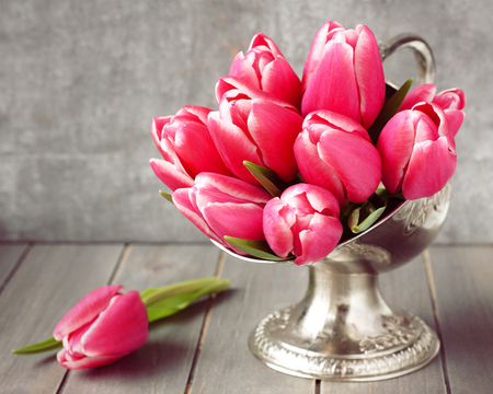 Bouquet of pink tulips in metal vase on wooden background photo