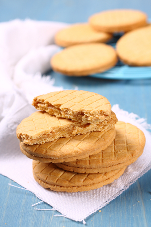 Stack of vanilla sandwich cookies on blue wooden background photo