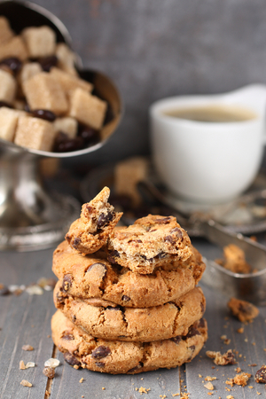 Fresh homemade chocolate chip cookies with cup of espresso on old wooden background photo