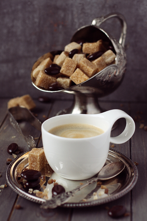 Taza de caf� express, cubos de az�car y dulces de chocolate en el fondo de madera r�stica Foto de archivo