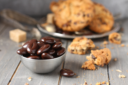Chocolate candy with chocolate chip cookies on wooden background photo